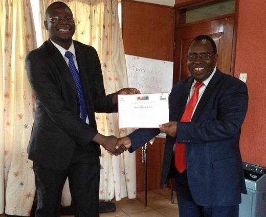 Jared Oundo receives a certificate from FBS Kariuki Senior careers officer moi University